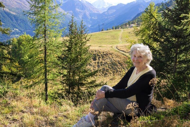 Äldre dam som tycker om en semester i bergen arkivbild
