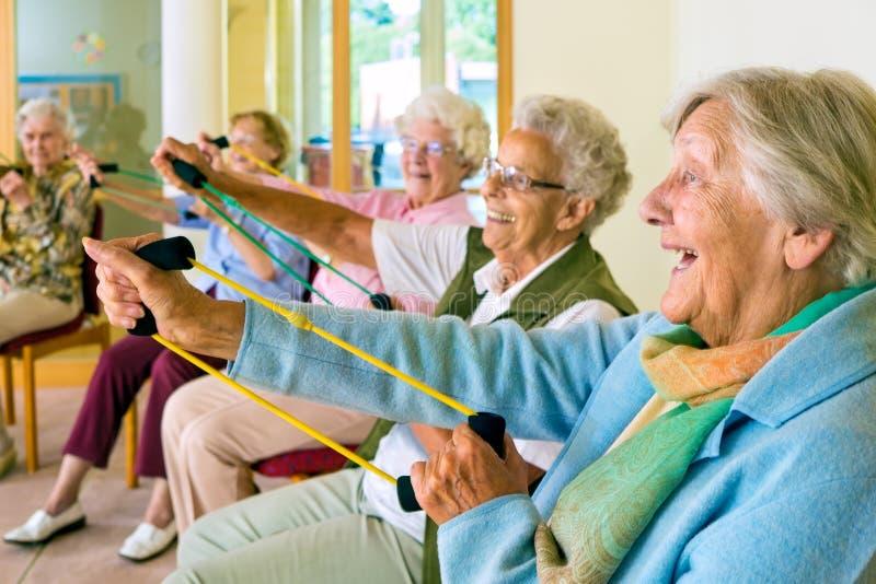 Äldre damer som övar i en idrottshall royaltyfri bild