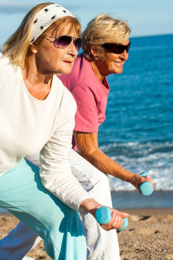 Äldre damer som gör worlout på stranden. arkivbild