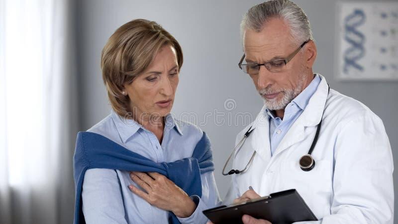 Äldre doktor som förklarar provresultat till den chockade damen, dyr medicin arkivbild