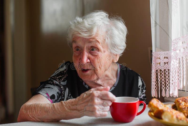 Äldre ensam kvinna som dricker te och samtal arkivbild