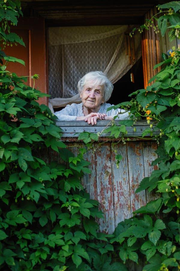 Äldre ensamma kvinnablickar från deras grönska terrasserar Ledset royaltyfri foto