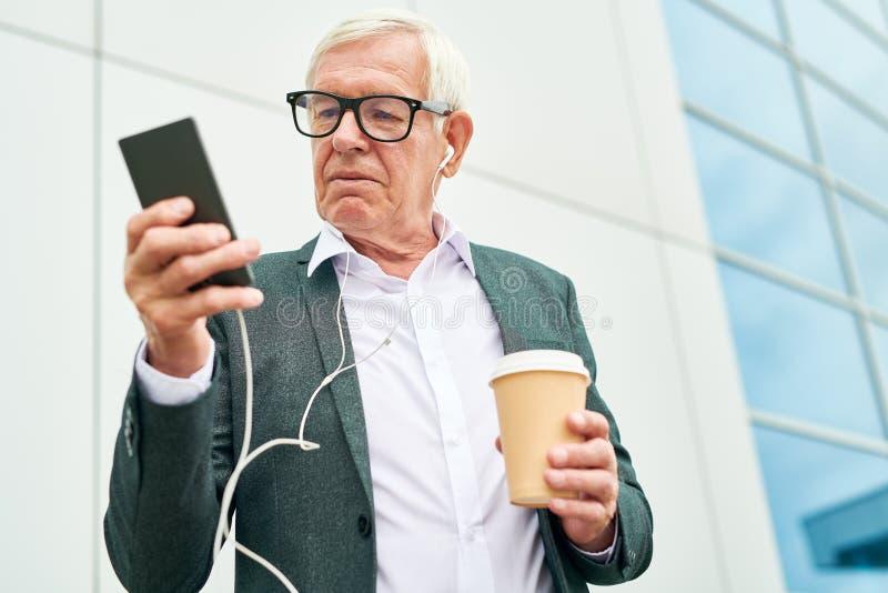 Äldre entreprenör med drinken genom att använda smartphonen fotografering för bildbyråer
