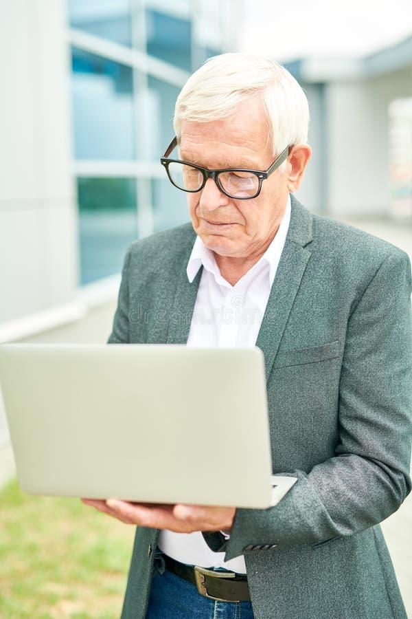 Äldre entreprenör som bläddrar bärbara datorn royaltyfri foto