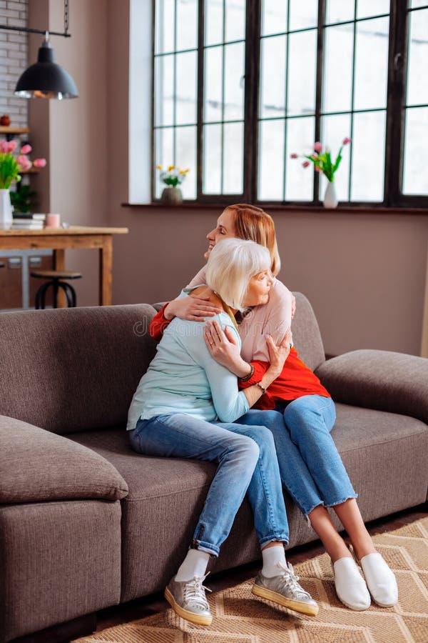 Äldre farmor som har en kram med den attraktiva sondottern på soffan arkivfoton