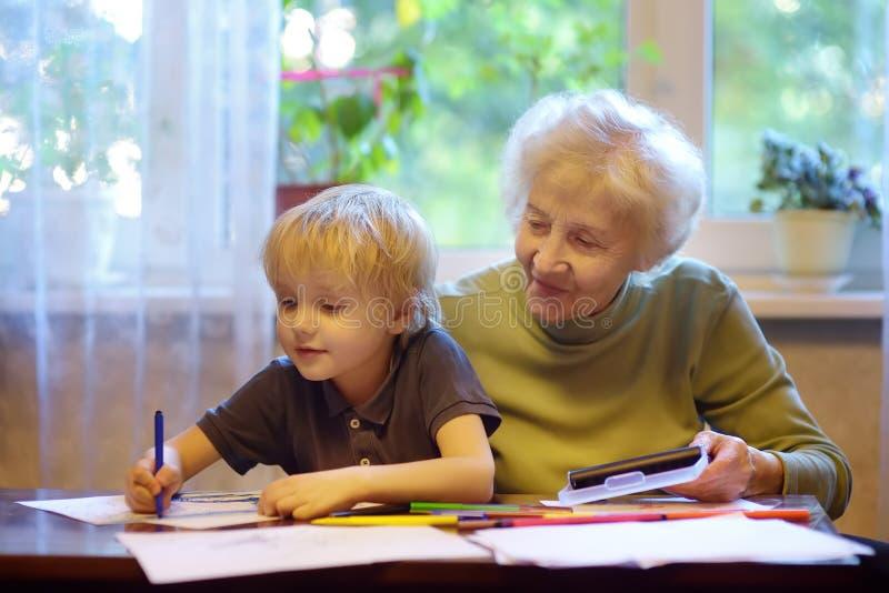 Äldre farmor som hjälper små barnbarn att göra hemläxor Mormor och sonson arkivbild