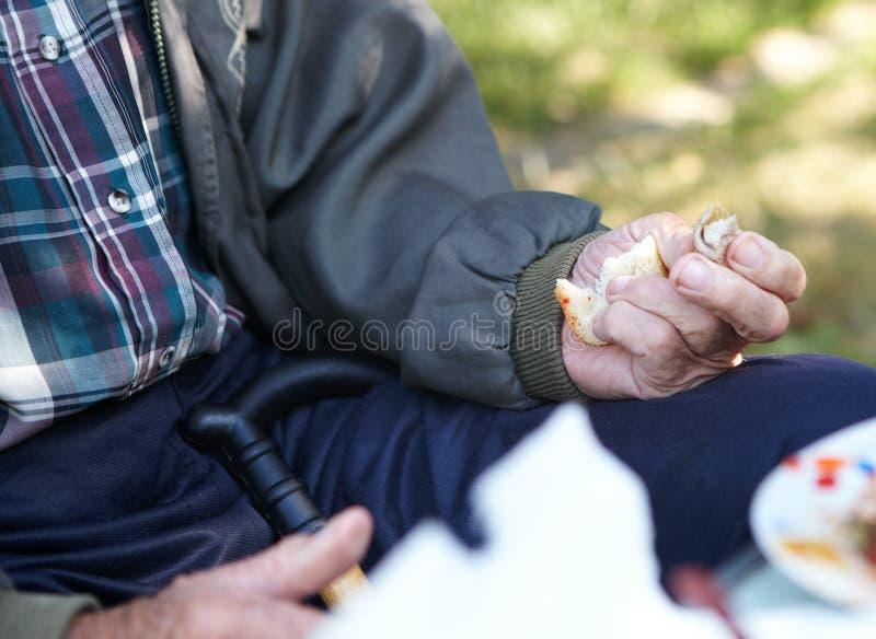 Äldre fattig man som äter bröd arkivbilder