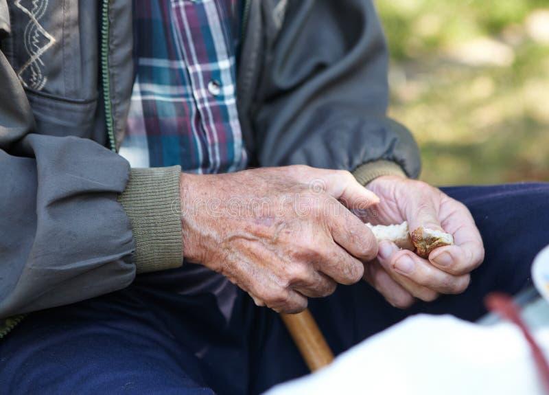 Äldre fattig man som äter bröd royaltyfri fotografi