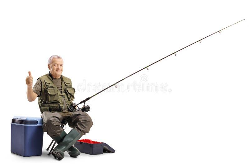 Äldre fiskare som rymmer upp hans tumme royaltyfria bilder