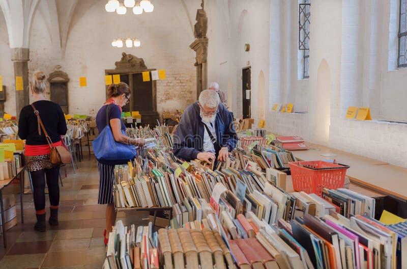 Äldre folk och barn som läser och köper böcker på loppmarknaden inom historisk kyrka royaltyfria foton