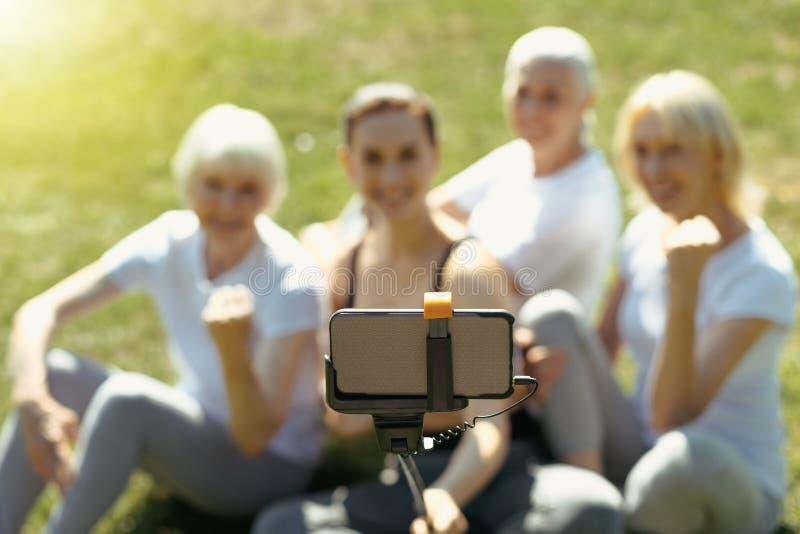 Äldre folk och lagledare som utomhus poserar för selfie arkivfoto