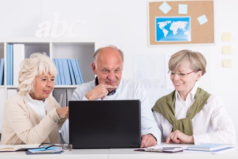 Äldre folk som använder bärbara datorn royaltyfria foton