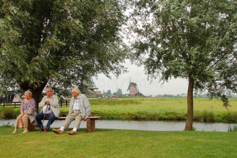 Äldre folk som sitter på en bänk bredvid en ström royaltyfria foton