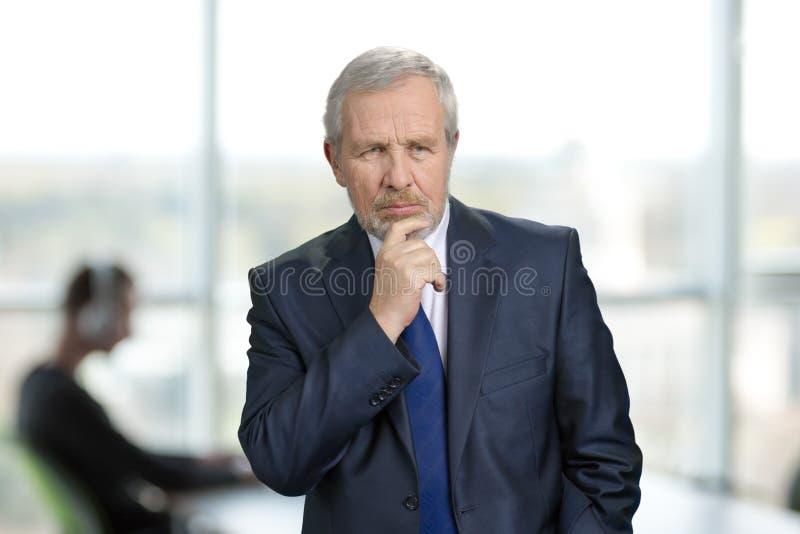 Äldre fundersam affärsman i ljus kontorsbakgrund royaltyfri bild