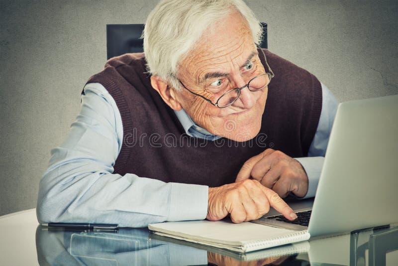 Äldre gamal man som använder sammanträde för bärbar datordator på tabellen arkivbild