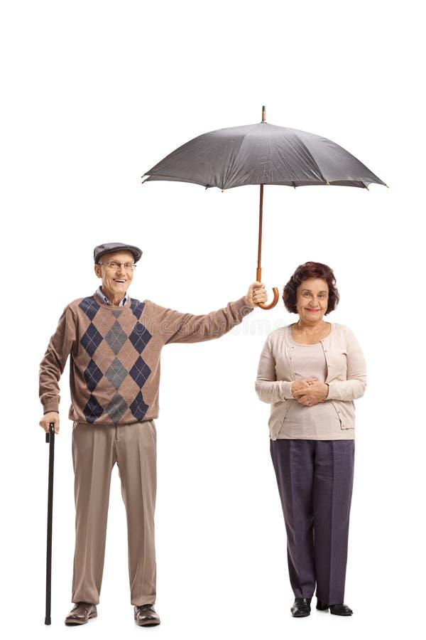 Äldre gentleman som rymmer ett paraply över en äldre kvinna arkivfoton