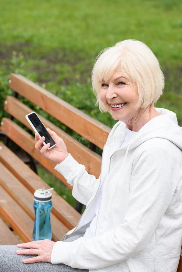 äldre gladlynt kvinna som använder smartphonen, medan sitta på bänk med sportflaskan royaltyfri foto
