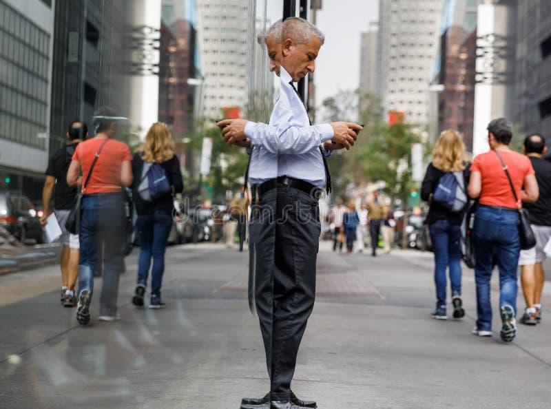 Äldre gråhårig man med en mobiltelefon i NYC arkivfoton