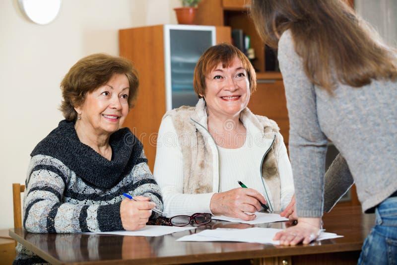 Äldre gulliga positiva kvinnor som gör skallr på det offentliga notarius publicukontoret royaltyfria bilder
