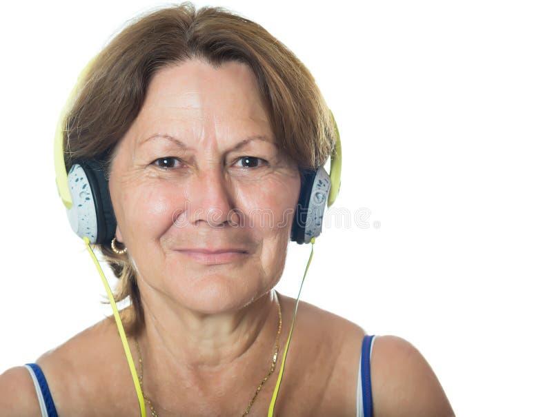 Äldre hög latinamerikansk kvinna som lyssnar till musik på hennes hörlurar royaltyfri fotografi
