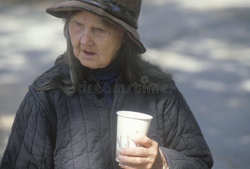 Äldre hemlös kvinna som dricker koppen kaffe, Chicago, Illinois arkivfoto