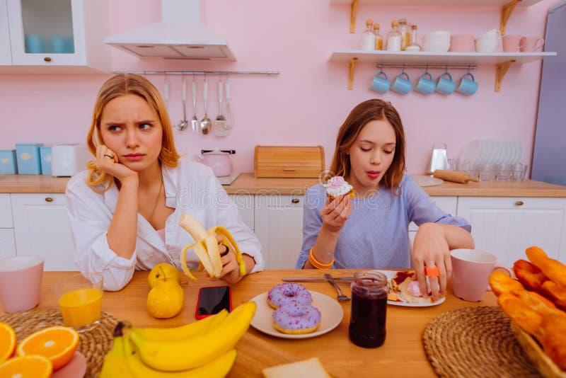 Äldre ilsken systerkänsla medan tonårs- sibling som äter sjuklig mat royaltyfri bild