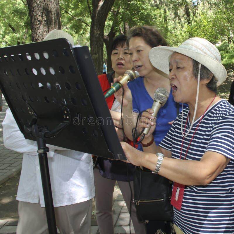 Äldre kinesiska kvinnor tycker om att sjunga i en parkera i Peking royaltyfri foto