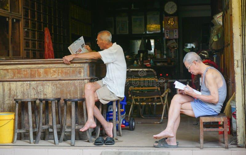 Äldre kinesiska män som läser tidningen arkivbild
