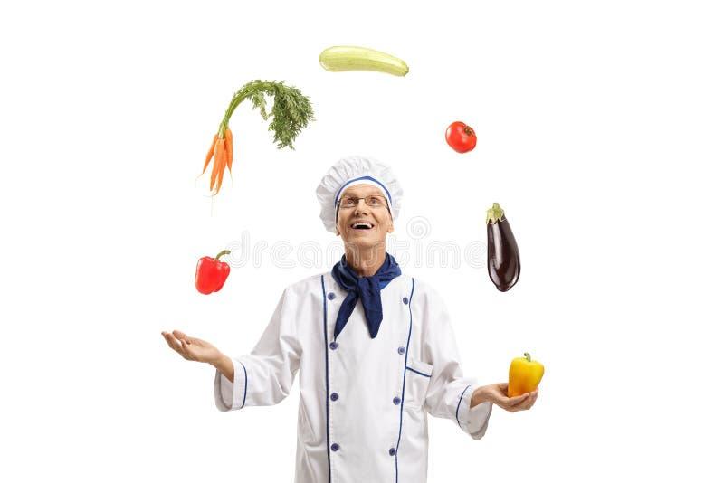 Äldre kock som jonglerar med grönsaker arkivbild