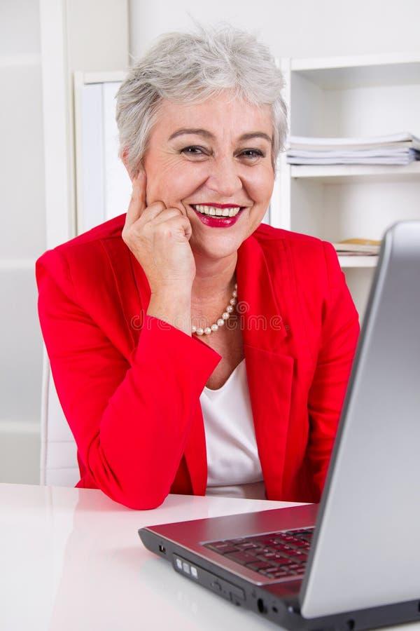 Äldre kontorsarbetare med bärbara datorn royaltyfri fotografi