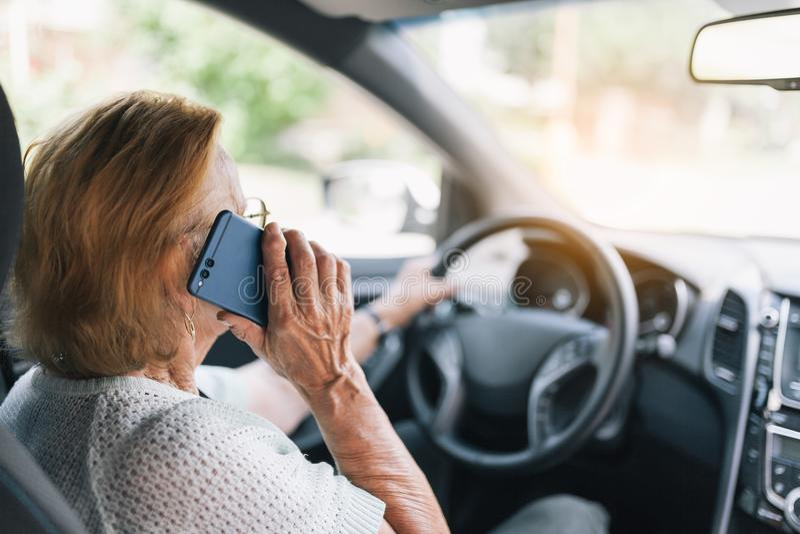 Äldre kvinna bak styrninghjulet genom att använda hennes telefon arkivbild