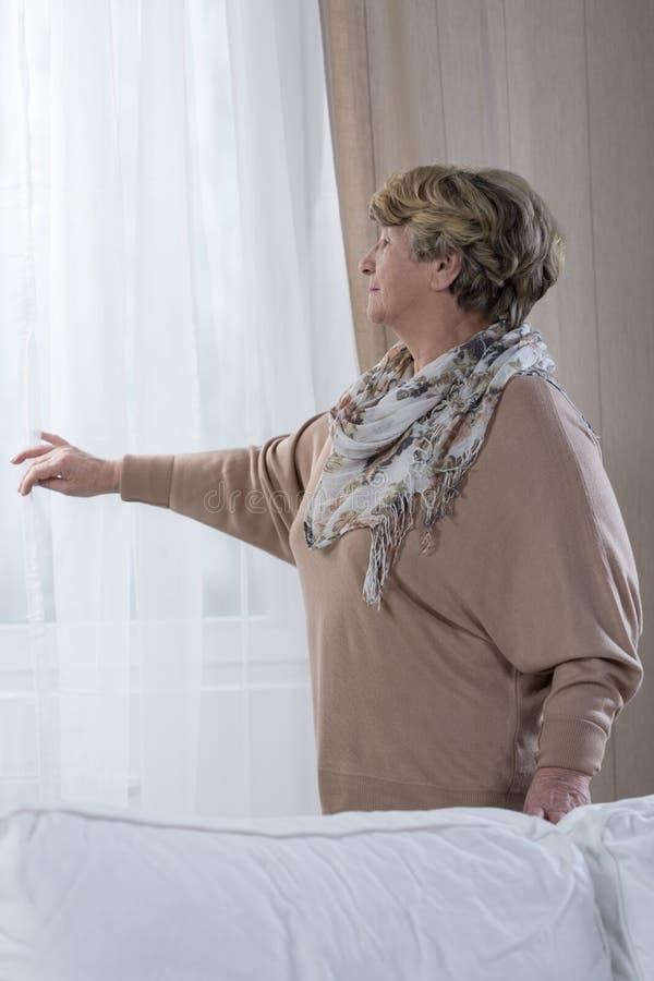 Äldre kvinna hemma arkivbild