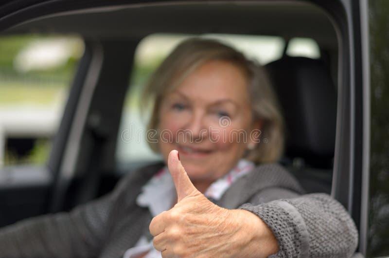 Äldre kvinna i en bil med tummen upp royaltyfri bild