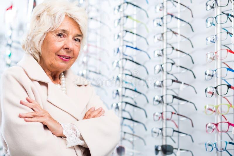 Äldre kvinna i optikerlager royaltyfri fotografi