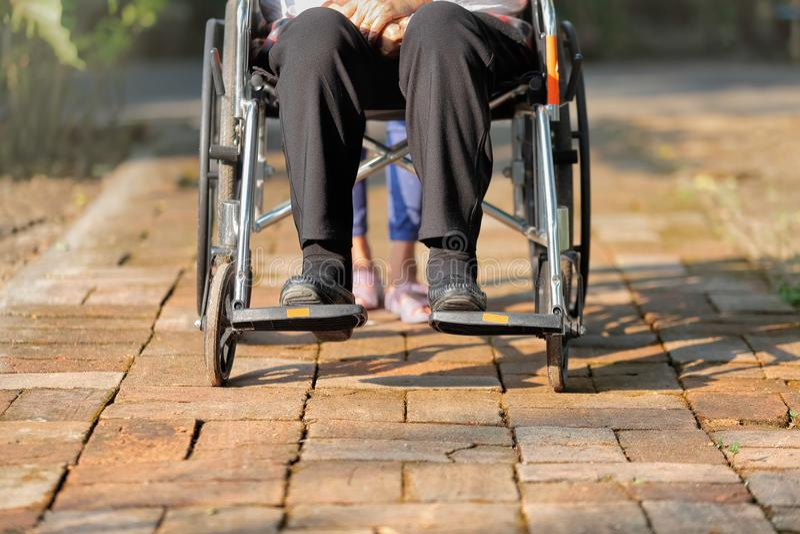 Äldre kvinna i rullstol med anhörigvårdaren royaltyfria foton