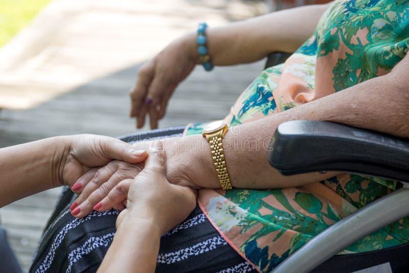 Äldre kvinna i rullstolinnehavhänder med anhörigvårdaren royaltyfri fotografi