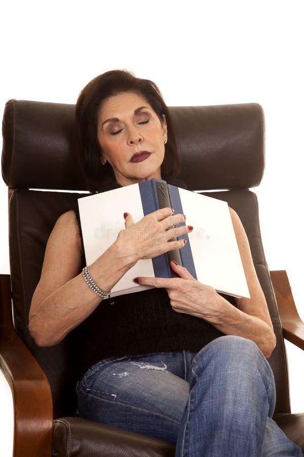 Äldre kvinna i stol med den sovande boken royaltyfri bild