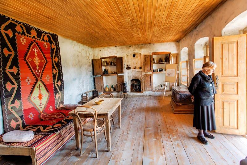 Äldre kvinna inom hus-museet av den berömda georgiska målaren Niko Pirosmani i by var han bodde sista år royaltyfri fotografi