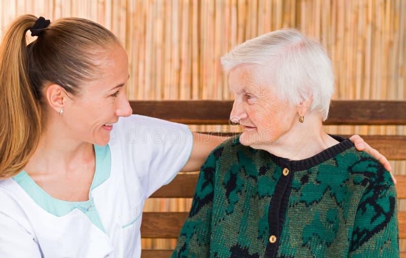 Äldre kvinna med anhörigvårdaren arkivfoton
