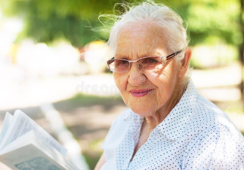 Äldre kvinna med boken fotografering för bildbyråer