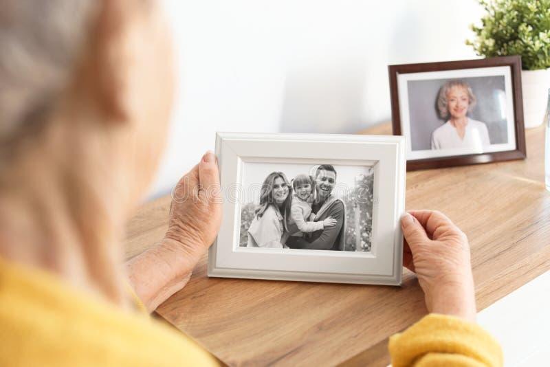 Äldre kvinna med den inramade familjståenden arkivbild