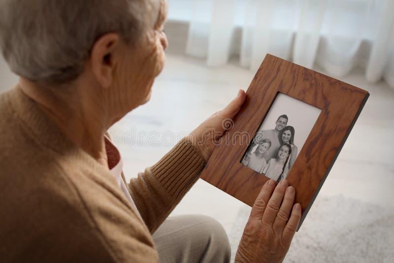 Äldre kvinna med den inramade familjståenden arkivfoton