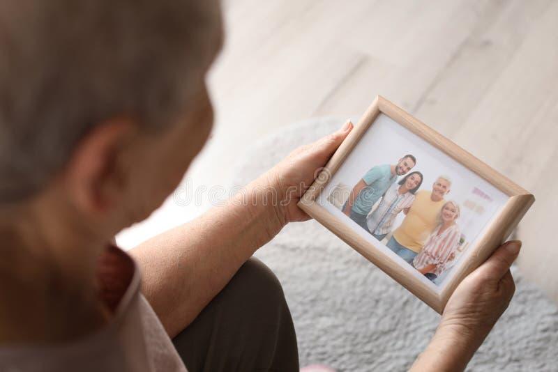 Äldre kvinna med den inramade familjståenden arkivfoto