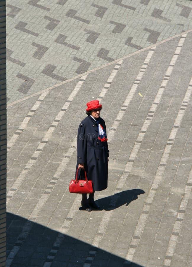 Äldre kvinna med den röda hatten och påsen royaltyfri foto