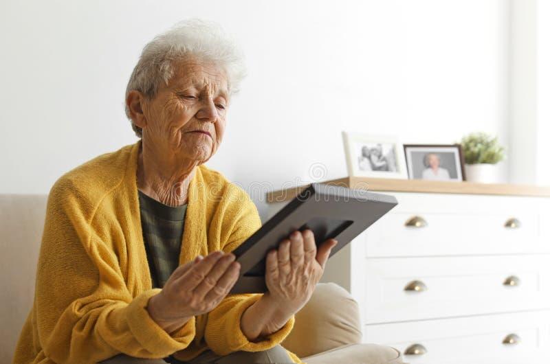 Äldre kvinna med det inramade fotoet på soffan arkivbilder