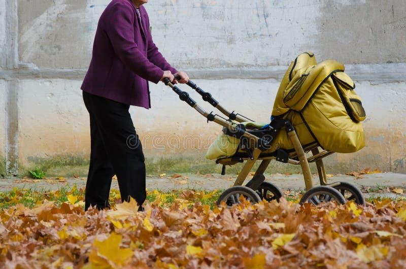 Äldre kvinna med en barnvagn gå på gul lövverk Äldre kvinna som in rider en sittvagn på trottoaren av en tom väg fotografering för bildbyråer
