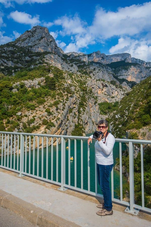 Äldre kvinna med en kamera på bron royaltyfria bilder