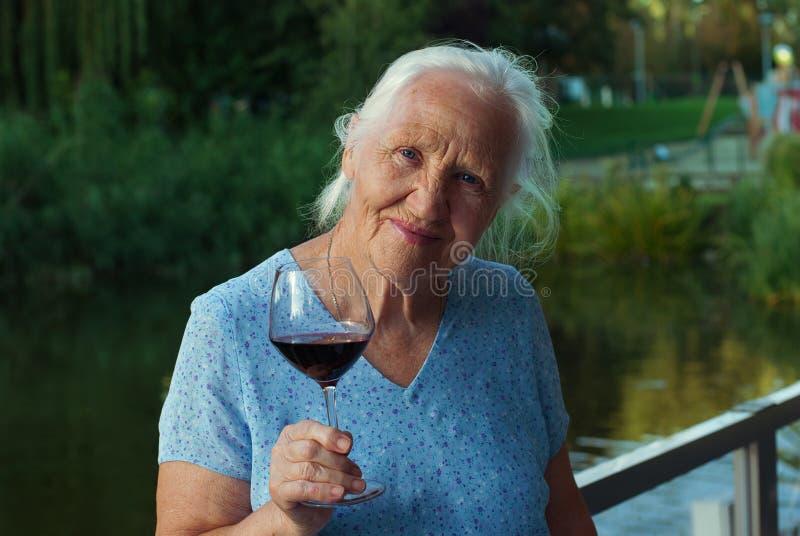 Äldre kvinna med exponeringsglas av vin arkivfoto