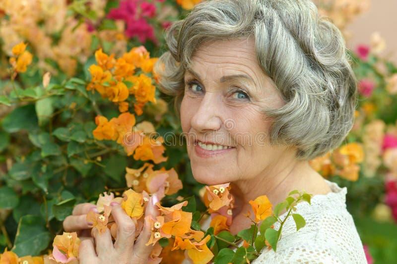 Äldre kvinna med gula blommor arkivfoto