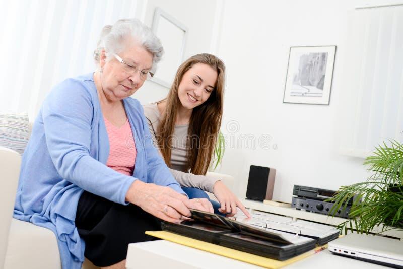 Äldre kvinna med hennes hemmastadda seende minne för ung sondotter i familjfotoalbum arkivfoto